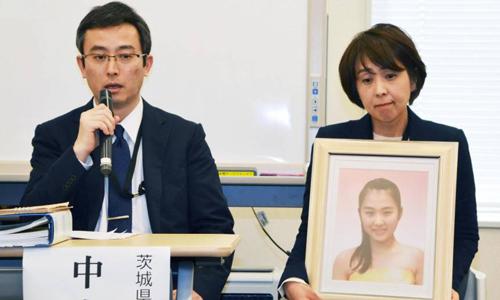 Phụ huynh cầm di ảnh của Naoko Nakashima - một học sinh trung học ở tỉnh Ibaraki tự tử hồi tháng 11/2015, phát biểu tại một hội thảo về vấn đề bắt nạt học đường tại Tokyo hồi tháng 3/2017. Ảnh: Kyodo.