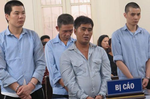 Khoan (hàng sau, thứ hai từ trái sang) và Tùng (ngoài cùng bên phải) cùng các bị cáo tại phiên tòa sơ thẩm.