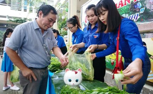 Giáo viên bỏ tiền vào hủ heo đất khi mua rau. Ảnh: Thạch Thảo.