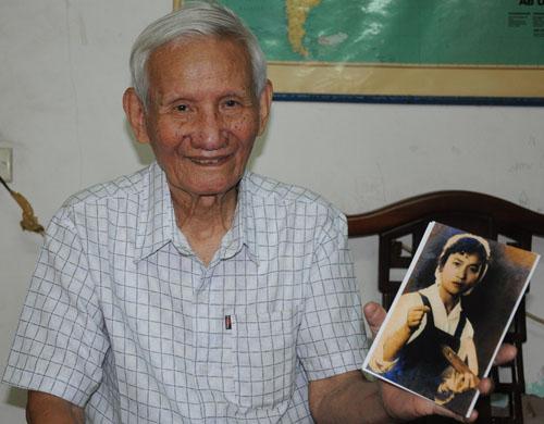 Ông Đặng Minh Phương và bức ảnh nữ công nhân dệt may. Ảnh: Viết Tuân.