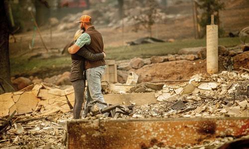 Cặp vợ chồng ôm nhau giữa ngôi nhà đã bị ngọn lửa thiêu hủy hoàn toàn tại thị trấn Paradise hôm 12/11. Ảnh: AP.