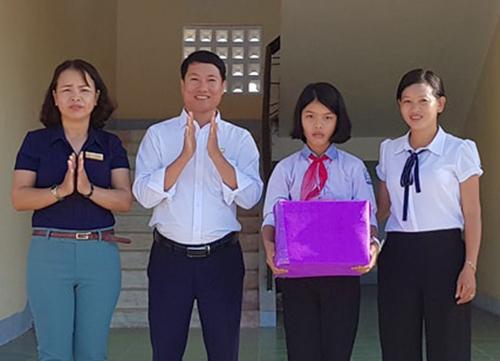 Tùng Lâm (thứ hai từ trái sang) nhận quà từ Ban giám hiệu. Ảnh: Đ.H