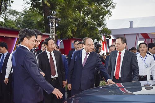 Ông Phạm Nhật Vượng (cavat đỏ) giới thiệu xe sedan cho Thủ tướng Nguyễn Xuân Phúc.
