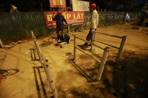 Công nhân lắp rào chắn trên vỉa hè đường Tố Hữutrong đêm. Ảnh: Gia Chính