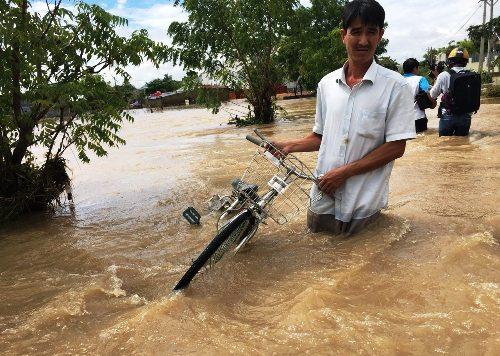 Nước ngập quá đầu gối khiến người dân Ninh Thuận đi lại khó khăn. Ảnh: Thanh Châu.