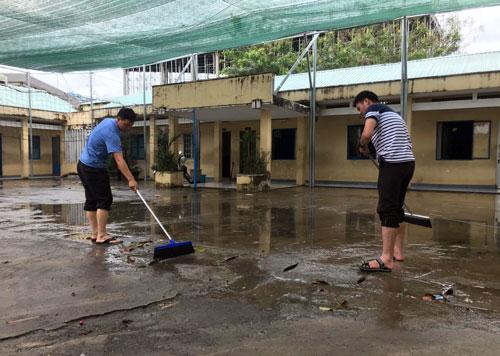 Giáo viên trường THCS An Phú Đông (quận 12) dọn dẹp sân trường khi nước đã rút. Ảnh: Mạnh Tùng.