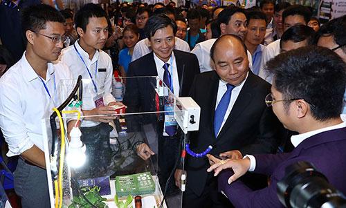 Thủ tướng và các đại biểu tham quan gian hàng giới thiệu công nghệ của startup. Ảnh: Nguyễn Đông.