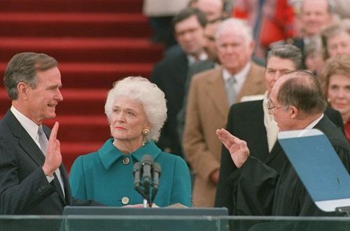 Bush tuyên thệ nhậm chức bên ngoài Đồi Capitol (Quốc hội Mỹ) ngày 20/1/1989, bên cạnh là đệ nhất phu nhân Barbara Bush. Ảnh: AP.