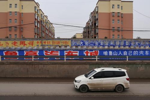 Bức tường ngăn cách khu dân cư và đường công cộng được lấp kín bằng quảng cáo của một đại lý ôtô địa phương ở Bình Đỉnh Sơn. Ảnh:Reuters/Yilei Sun