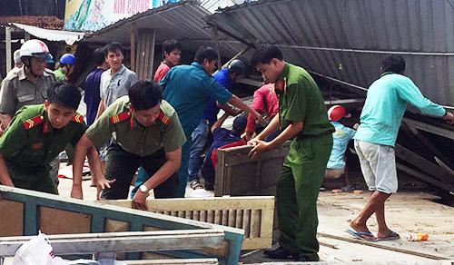 Các lực lượng hỗ trợ người dân bị sạt lở tháo dỡ nhà cửa, thu dọn tài sản. Ảnh: An Phú