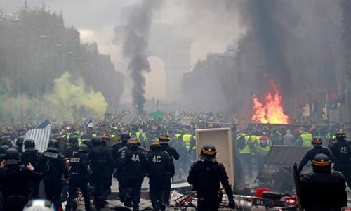 Người biểu tình mặc áo khoác vàng chạy khỏi cảnh sát trên đại lộ Champs-Elysees ở Paris hôm 1/12. Ảnh: Reuters.