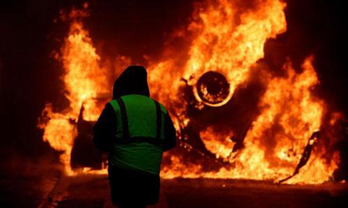 Một người biểu tình mặc áo vàng nhìn chiếc ôtô bị đốt cháy gần đại lộ Champs-Elysees hôm 1/12. Ảnh: CNN.