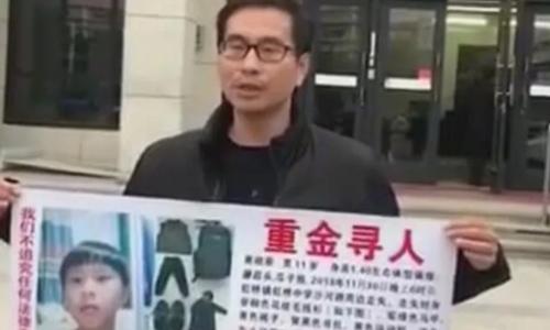 Người bố giơ ảnh tìm kiếm con trai. Ảnh: Weibo.