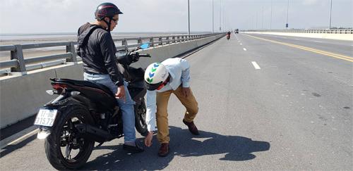 Một số người dân tham gia giao thông phát hiện đinh đãdừng xe nhặt nhưng không xuể.Ảnh: Giang Chinh