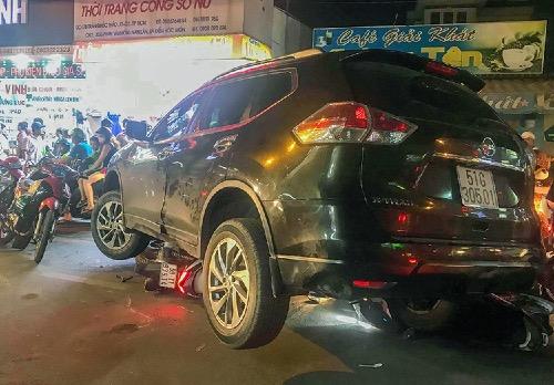 Ôtô nằm chênh vênh trên một loạt xe máy. Ảnh: Sơn Hoà.