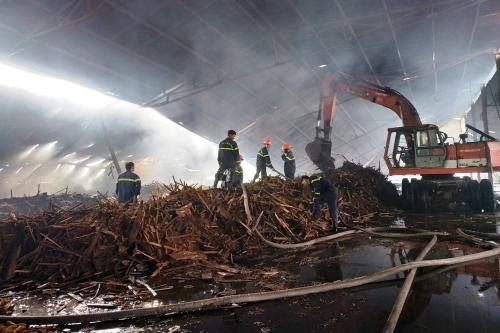 Nhiều chiến sĩ cứu hỏa phun nước dập tắt đám cháy. Ảnh: Thạch Thảo.