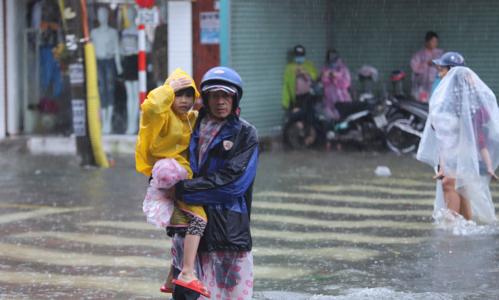 Mưa lớn và ngập sâu ở nhiều tuyến đường khiến việc đi lại của người dân gặp khó khăn. Ảnh: Nguyễn Đông.
