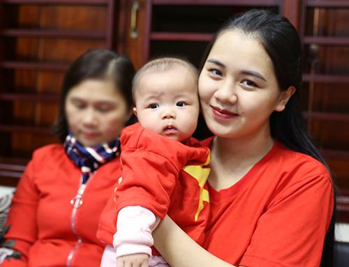 Chị Phương cùng con gái Sunny mặc áo cờ đỏ sao vàng cổ vũ cho chồng. Ảnh: Đức Hùng