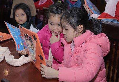 Học sinh Trường Tiểu học Kim Liên tò mò với sản phẩm áo gắn họa tiết phản quang.Ảnh: V. Hậu.