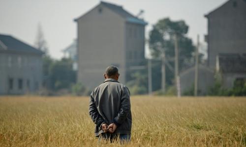 Một người đàn ông đứng giữa cánh đồng nhìn về phía ngôi nhà cao tầng ở vùng nông thôn Trung Quốc. Ảnh: AFP.