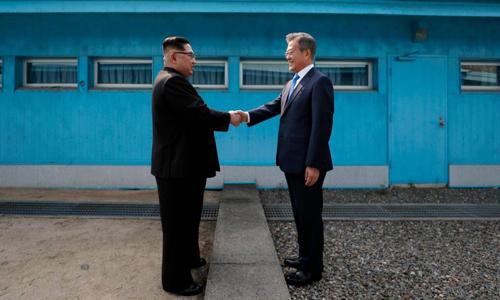 Lãnh đạo Triều Tiên Kim Jong-un (trái) bắt tay Tổng thống Hàn Quốc Moon Jae-in tại Đường Ranh giới Quân sự giữa hai nước hôm 27/4. Ảnh: AFP.