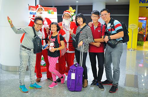 Nhiều du khách vui vẻ chụp ảnh với các ông già Noel tại sân bay. Ảnh: Anh Duy.