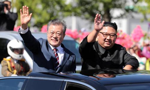 Tổng thống Hàn Quốc Moon Jae-in (trái) và lãnh đạo Triều Tiên Kim Jong-un vẫy tay với người dân