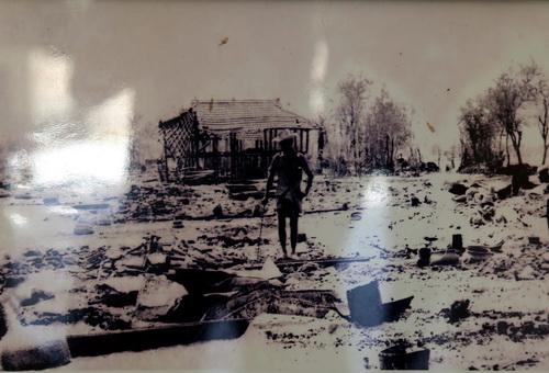 Một người đàn ông tìm kiếm tài sản trên nền nhà bị bọn Pol Pot đốt phá.
