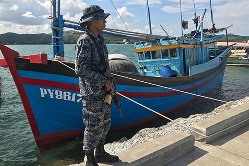 Binh sĩ Philippines đứng canh gần một tàu cá Việt Nam bị bắt giữ vào tháng 9/2017. Ảnh: ABS-CBN News