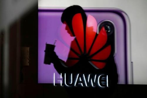 Một người đi qua logo của Huawei ở Trung Quốc. Ảnh: Reuters.