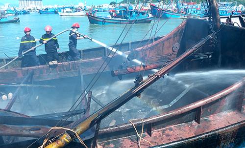 Cảnh sát chữa cháy phun nước dập lửa trong tàu cá cháy trong cảng ở Nha Trang. Ảnh: Xuân Ngọc