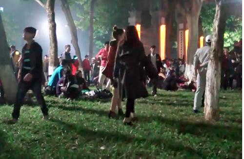 Nhiều bạn trẻ giẫm lên thảm cỏ khu vực đền Ngọc Sơn dịp Tết Dương lịch 2017. Ảnh: Trần Quang.
