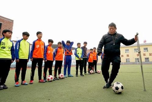 Liệt nửa người, thầy giáo Trung Quốc chống nạng dạy đá bóng - ảnh 1
