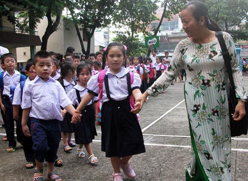 Cô giáo chủ nhiệmnhậnhọc sinh lớp 1 trong ngày tựu trường tại TP HCM. Ảnh: Mạnh Tùng.