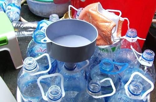 Những chai nước khoáng đã qua sử dụng được bà Mùa mua lại để đựng giấm pha bằng axit. Ảnh: Văn Nam.