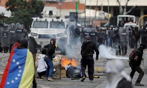 Người biểu tình đụng độ lực lượng an ninh tại Caracas ngày 23/1. Ảnh: AFP.