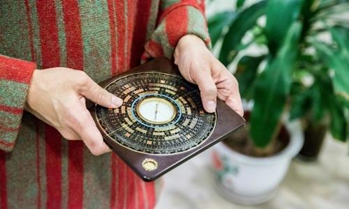 Thầy phong thủy sử dụng la bàn để tìm hướng xuất hành hay đặt đồ vật có lợi cho sức khỏe, tài lộc. Ảnh: AFP.