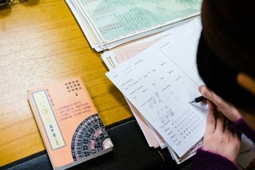 Thầy phong thủy sử dụng biểu đồ và bảng tính toán để dự đoán tương lai. Ảnh: AFP.