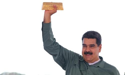 Tổng thống Venezuela Nicolas Maduro cầm một thỏi vàng trong cuộc gặp với các đại diện ngành khai thác khoáng sản ở Puerto Ordaz hồi cuối năm 2017. Ảnh: Reuters.