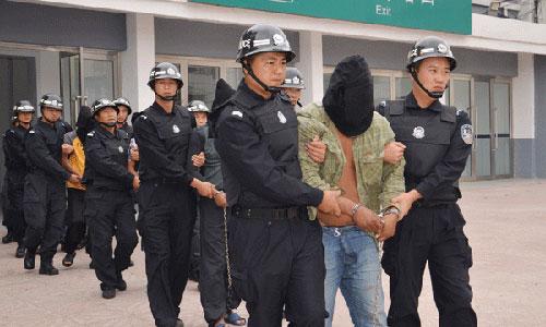 Cảnh sát Trung Quốc áp giải tội phạm. Ảnh: ChinaDaily.