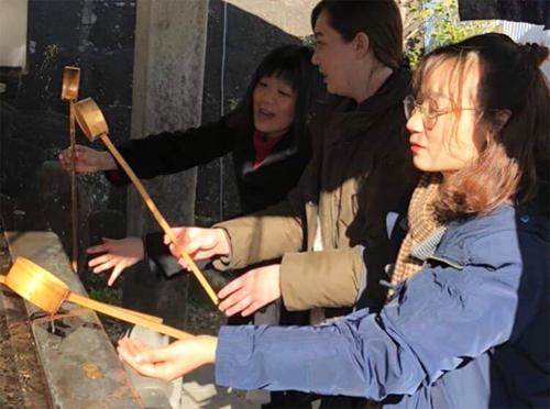 Oanh (ngoài cùng bên phải) cùng mọi người làm lễ rửa tay ở chùa.