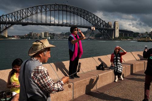 Một nhóm du khách Trung Quốc chụp ảnh tại cầu Harbour gần Nhà hát Opera Sydney hồi tháng 1. Ảnh: NYT.