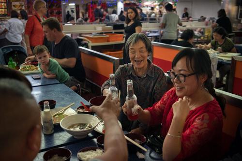 Nhóm du khách ăn tối tại một nhà hàng ở khu China Town ở Sydney. Ảnh: NYT.