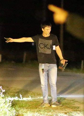 Trung cầm súng, lựu đạn đứng trước hàng trăm cảnh sát. Ảnh: HT