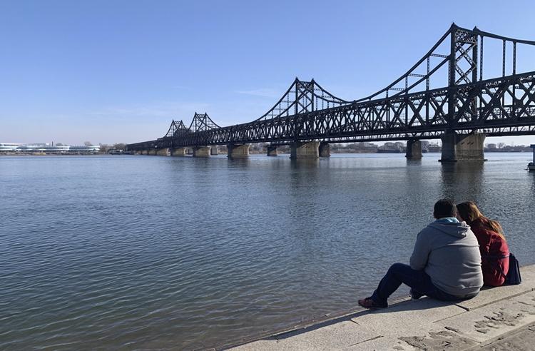 Người dân ngồi bên sông Áp Lục ở Đan Đông, nhìn sang bên kia Triều Tiên hôm 23/2. Ảnh: AP.