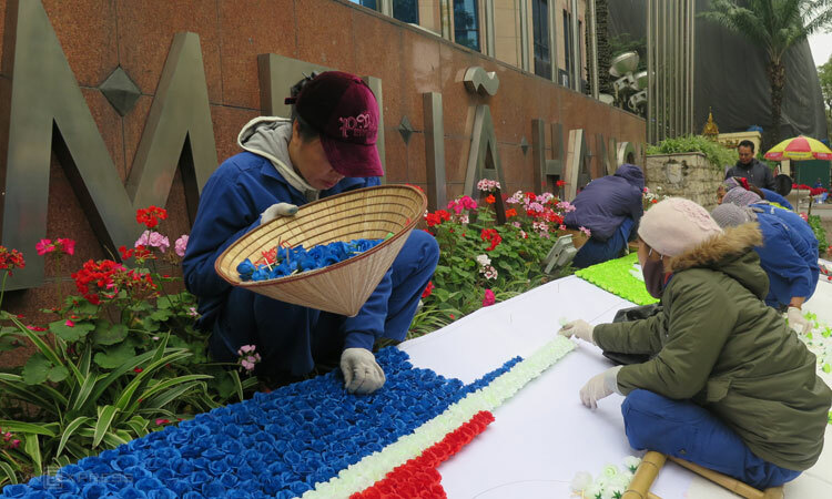 Các công nhân đang cắm hoa tạo hình quốc kỳ hai nước Việt Triều. Ảnh: Việt Dũng.