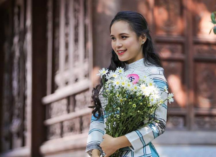 Phương Linh mặc áo dài, chụp ảnh với cúc họa mi. Ảnh: NVCC