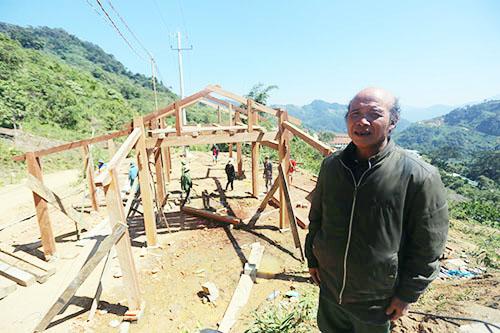 Ông Hồ Văn Díu giám sát thợ thi công căn nhà gỗ. Ảnh: Đắc Thành.