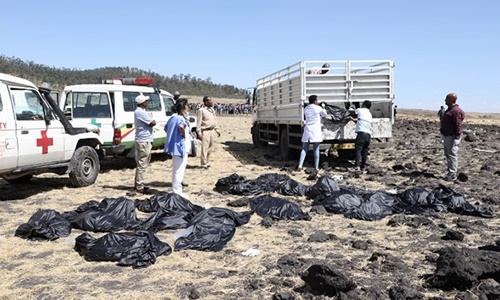 Nhân viên cứu hộ tại hiện trường vụ tai nạn thu thập các thi thể, bọc trong túi nilon và chuyển đi. Ảnh: Reuters.