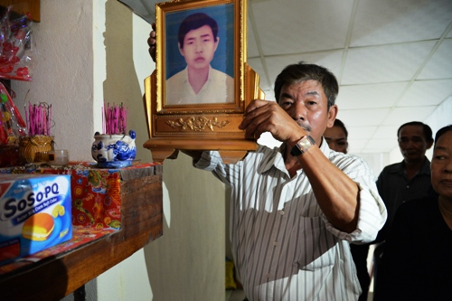 Ông Bình dỡ bỏ bàn thờ của em trai sau ngày đoàn tụ. Ảnh: Phương Linh.
